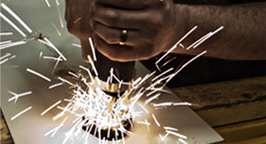 Man cutting metal as sparks fly