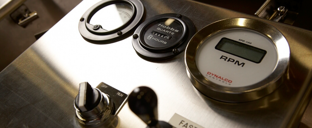 Close up image of the front of a control panel with dials and gauges